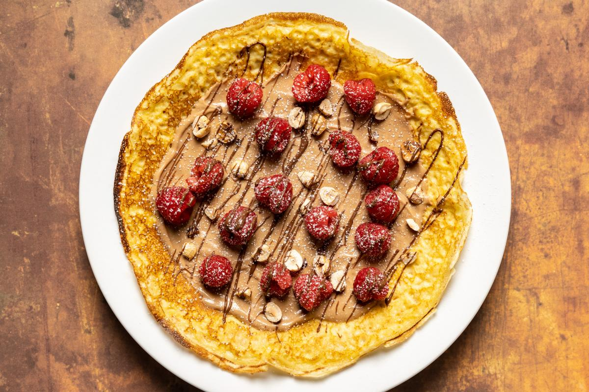 sweet brandy batter crepe with hazelnuts, hazelnut spread, raspberries and chocolate drizzle