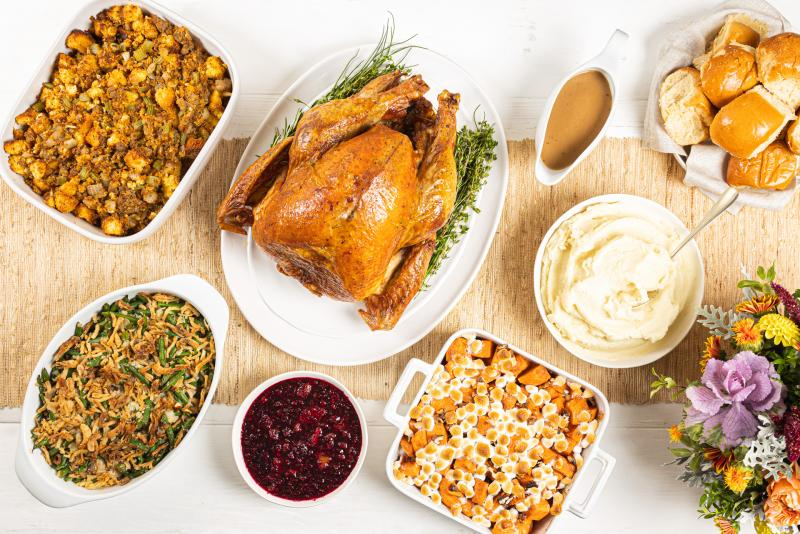 Holiday meal with roasted turkey, stuffing, mashed potatoes, green bean casserole, sweet potato casserole, rolls and cranberry sauce